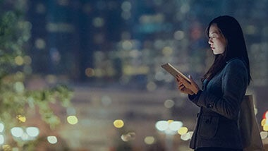 Woman staring at tablet with blurred city lights